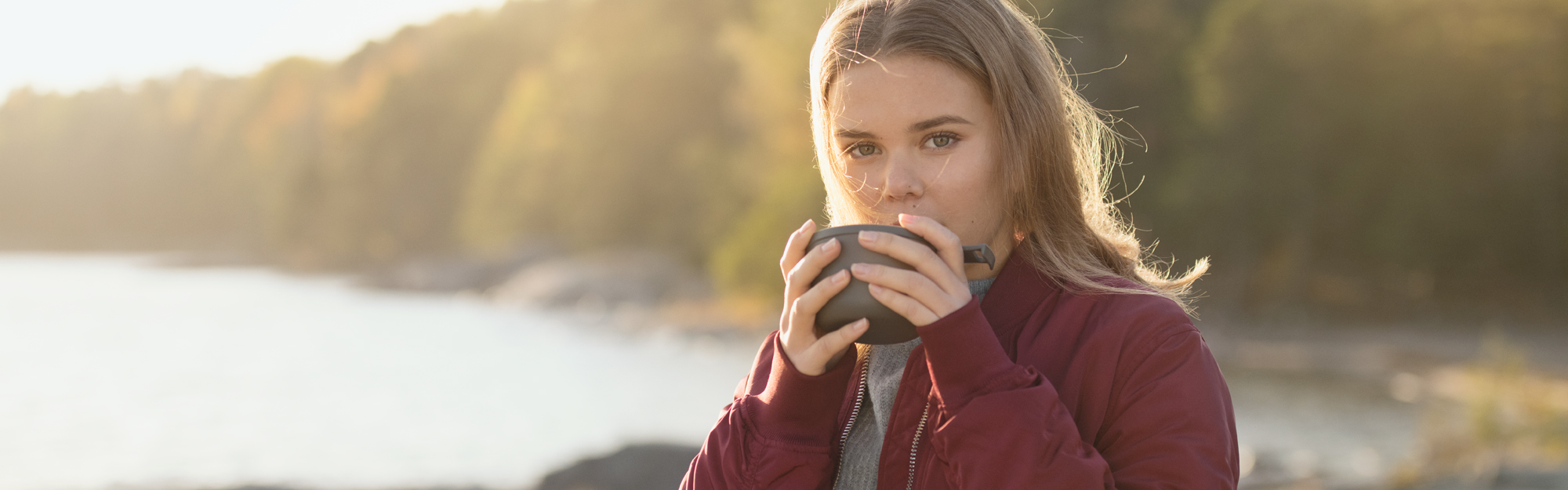 Young woman drinking a hot beverage by the sea