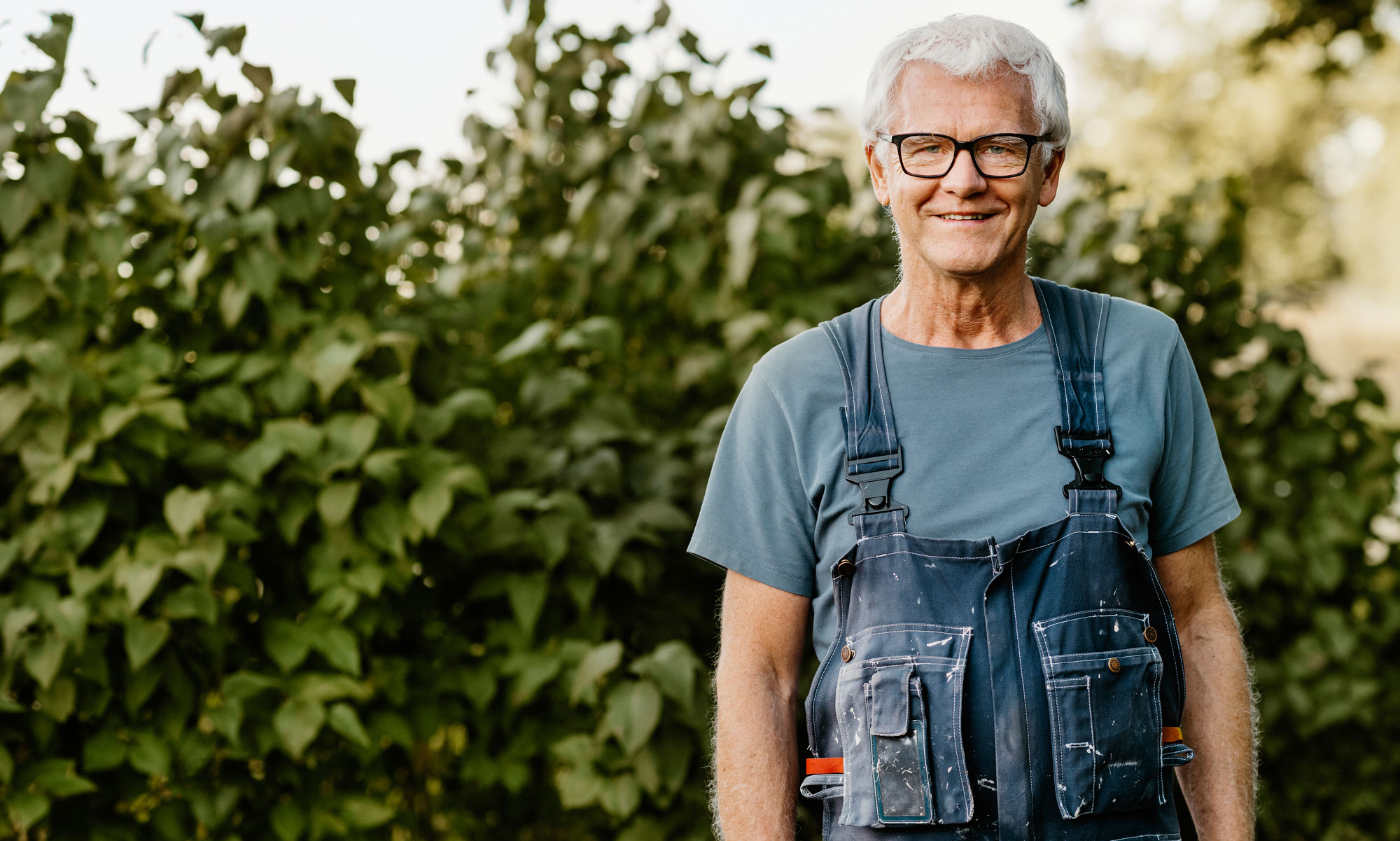 Older man outdoors in overalls